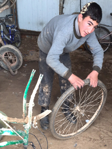 A child in Zaatari repairing a bicycle.
